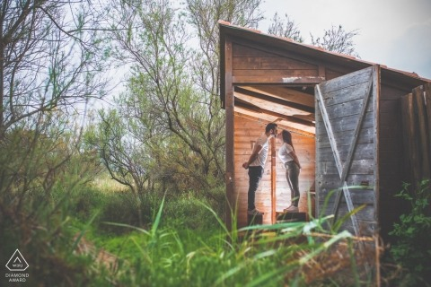 The bride stand on crates and kiss in a small hut during their Priolo engagement photoshoot by a Sicily photographer.