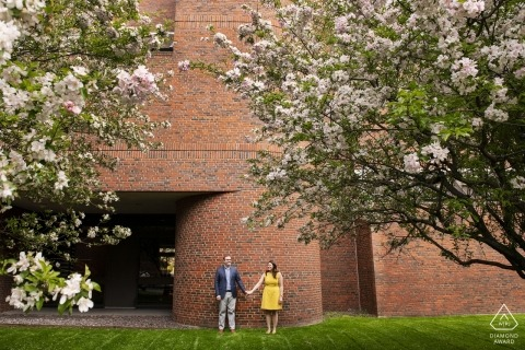 Cambridge, Massachusetts Engagement Couple Shoot - Wide shot met kersenbloesems en bakstenen muur