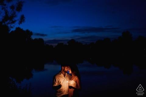 Ein Paar hält ein kleines Licht an, als sie nachts in London während ihres Vorhochzeitsshootings eines englischen Fotografen zusammenstehen.