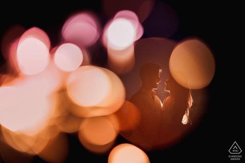 Das Paar steht auf der anderen Seite eines runden Fensters und wird während der Verlobungssitzung von einem Fotografen aus London, England, von Lichtern umstrahlt