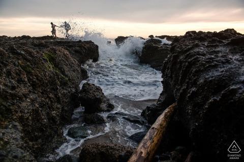 Laguna Beach, CA pareja engagede pasear por las rocas en Laguna Beach.