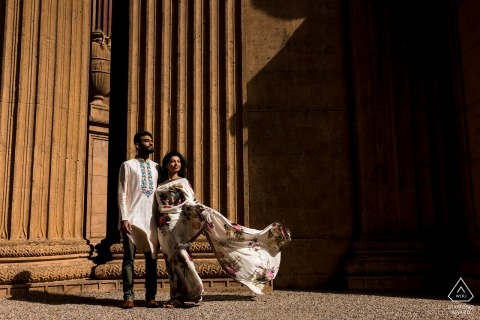 The couple appears statuesque as they stand in front of the Palace of Fine arts in this engagement portrait by a San Diego, CA photographer.