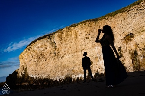 Haifisch-Flossen-Bucht-Vorhochzeits-Porträt - die Silhouette des Paares gegen die Küstenklippen