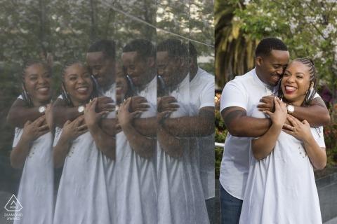 Ein Paar spiegelt sich auf einer polierten Steinoberfläche auf dem Union Square wieder, während sie sich während ihres Fotoshootings vor der Hochzeit von einem Fotografen aus San Francisco, Kalifornien, gegenseitig festhalten.