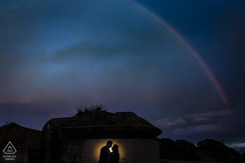 A couple stands silhouetted by a small light on Hawk Hill during their engagement photoshoot by a San Francisco, CA photographer.