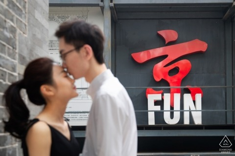 """A man kisses his fiance's forehead in front of a sign reading """"FUN"""" in this engagement photo by a Beijing, China photographer."""