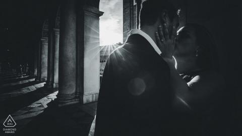 Ein Paar küsst sich, während die Sonne durch große Säulen in diesem Schwarzweiss-Porträt vor der Hochzeit eines venezianischen Fotografen strahlt.