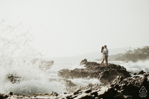 A couple kisses as they stand on rocks with waves crashing nearby in San Francisco during their pre-wedding session by a Sacramento, CA photographer