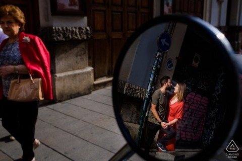 A couple is reflected in a car mirror as they hold hands on the sidewalk in this engagement photo by an Alicante, Valencia photographer.