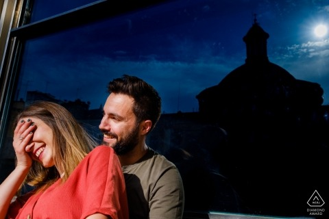 A man and woman laugh as they stand in front of a window at nighttime in this pre-wedding photoshoot by an Alicante, Valencia photographer.