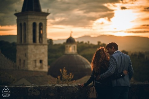 A couple stands in front of a tower in Spoleto and kisses as the sun sets during their engagement photo session by Perugia, Umbria photographer.