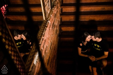 A man and woman hold hands in a cabin in Rio das Otras as they are reflected in the mirror above them in this engagement photo by a Rio de Janeiro photographer.