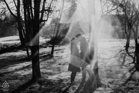 A couple in Lorient, France kisses as light refracts off the morning dew in this black and white pre-wedding photo by a Morbihan, Brittany photographer.