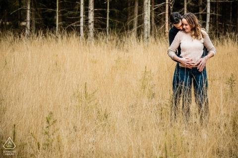 擁抱在領域的從事的夫婦室外照片在他們的在Landgoed小室Treek的訂婚射擊期間