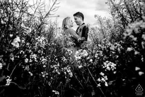 Una pareja se mira mientras se encuentran en un campo de flores en esta foto en blanco y negro antes de la boda de un fotógrafo de Aachen, Renania del Norte-Westfalia.