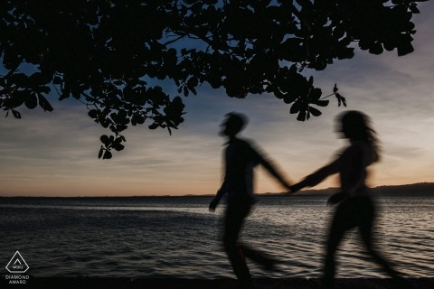 A silhouette of a couple holding hands as they walk along a lake can be seen in this engagement photo by a Santa Catarina, Brazil photographer.