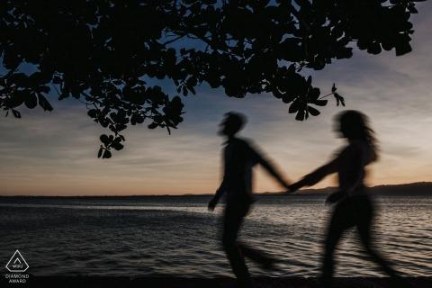 握手的夫妇的剪影,他们沿湖走在这张订婚照片能被看见由圣卡塔琳娜州,巴西摄影师。