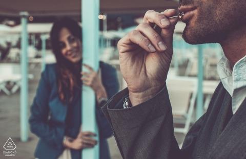 Eine Frau beobachtet ihren Verlobten, wie er während der Verlobungssitzung eines ligurischen Fotografen ein kleines Kruzifix im Forte dei Marmi küsst.