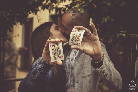 A couple holds up a Queen of Hearts and King of Hearts as they kiss beneath a tree in Bolano during their pre-wedding session by a Liguria photographer.