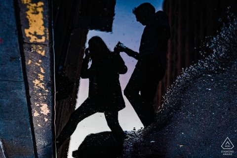 A man can be seen helping a woman cross the street in the reflection of a puddle during their pre-wedding photo session by a New York City photographer.