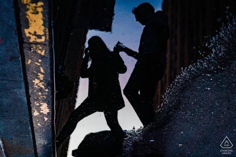 Widać mężczyznę, który pomaga kobiecie przejść przez ulicę w odbiciu kałuży podczas sesji zdjęciowej przed ślubem, wykonanej przez nowojorskiego fotografa.