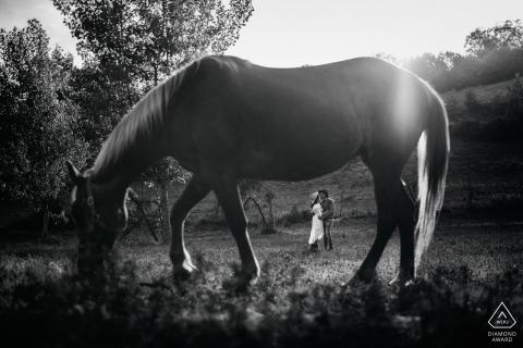 À Alvito, en France, on peut voir un couple debout dans un champ au loin derrière un cheval qui se trouve au premier plan sur cette photo de fiançailles capturée par un photographe de Lazio.