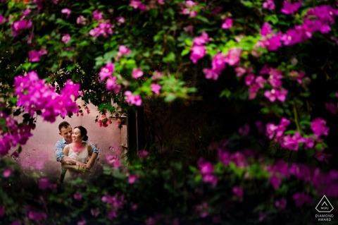 Een Saigon-paar kan worden gezien houdend elkaar in deze verlovingfoto genomen door purpere bloemen door een fotograaf van Ho Chi Minh, Vietnam.