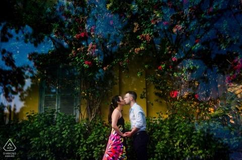 Een paar kussen 's nachts in een prachtige Saigon-tuin in deze verlovingfoto door een fotograaf van Ho Chi Minh, Vietnam.