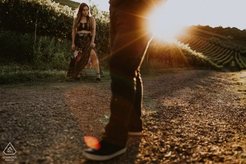 A couple stands on a dirt road in Bento Goncalves as the sun shines behind them during their engagement photoshoot by a Rio Grande do Sul, Brazil photographer.