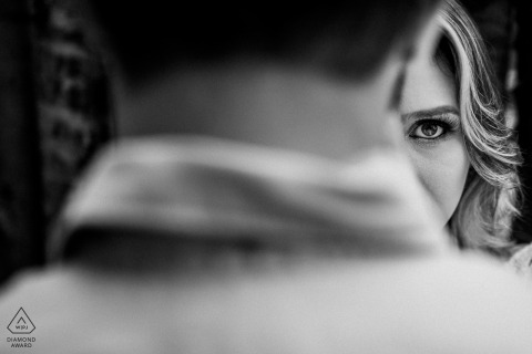 In Vitoria, half of a woman's face can be seen as her fiance stands in the foreground in this black and white engagement photo by a Rio Grande do Sul, Brazil photographer.