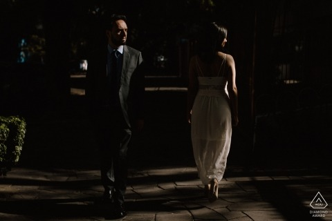 A couple passes one another at nighttime during this Porto Alegre engagement session by a Rio Grande do Sul, Brazil photographer.