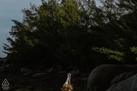 Een paar staat samen in de verte onder weelderige, groene bomen in Paraia do Rosa, Santa Catarina in deze verlovingsshoot door een fotograaf van Rio Grande do Sul.
