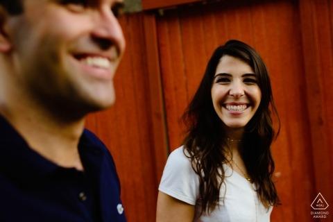 Eine Frau lächelt ihrem Verlobten zu, als sie während ihrer Fotosession vor der Hochzeit von einem Fotografen aus Minas Gerais, Brasilien, in Ouro Preto zusammenstehen.