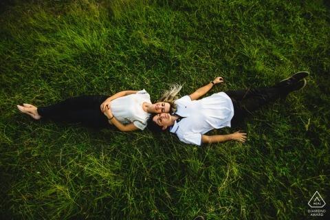 Ein Paar liegt Kopf an Kopf auf dem Rasen in Ouro Preto, während eines Fotoshootings eines Fotografen aus Minas Gerais, Brasilien.