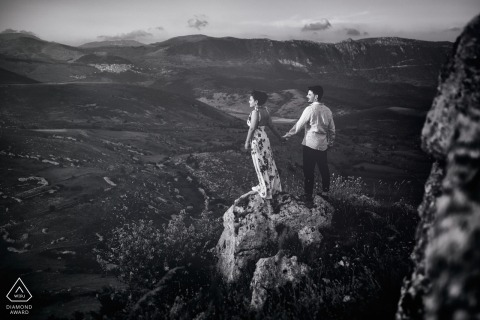 A couple holds hands as they stand on a boulder in Rocca Calascio overlooking the plains in this engagement session by a Lazio, Italy photographer.