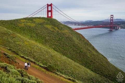 Una pareja camina por un camino de tierra cerca del puente Golden Gate de San Francisco en esta sesión de compromiso con un fotógrafo de California.