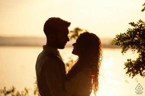 A couple stands in the golden sunlight of Bolsena, Italy in this engagement photo by a Orvieto photographer.