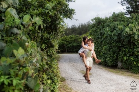 A man carries his fiance along a path through tall, green bushes in this engagement photoshoot by a Hualien County, Taiwan photographer.