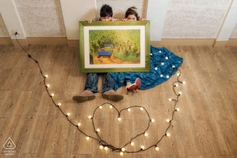 Una coppia si siede sul pavimento con in mano un quadro mentre una serie di luci disposte in un cuore giace sul pavimento di fronte a loro per il servizio fotografico pre-matrimonio di una fotografa di Hualien, Taiwan.