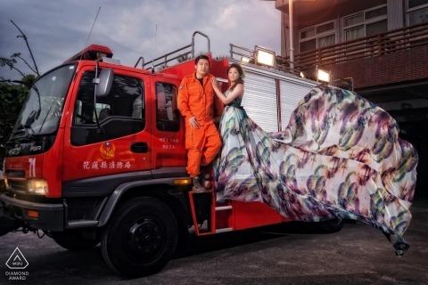 L'abito di una donna soffia drammaticamente nel vento mentre lei e il suo fidanzato stanno insieme su un grande camion rosso in questo ritratto di fidanzamento di una fotografa di Hualien, Taiwan.