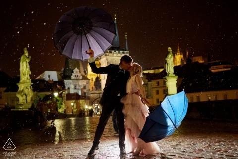 Podczas ulewnej ulewy ta zaangażowana para dzieli się pocałunkiem w Pradze podczas wieczornej sesji zaręczynowej na Moście Karola