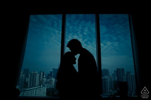A man kisses his fiance on the forehead as they stand near a window looking out on the night sky of Singapore in this engagement portrait by a Tamil Nadu, India photographer.