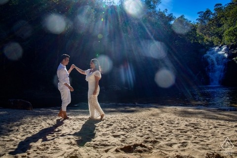 A man draws his fiance closer to him as they walk along the sand in the sunlight of Pirenopolis during their engagement photoshoot by a Goias, Brazil photographer.