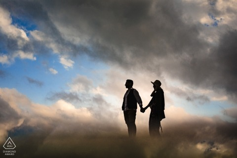 A couple holds hands and walks together in Mersin through clouds reflected around them in this pre-wedding photo by an Istanbul, Turkey photographer.