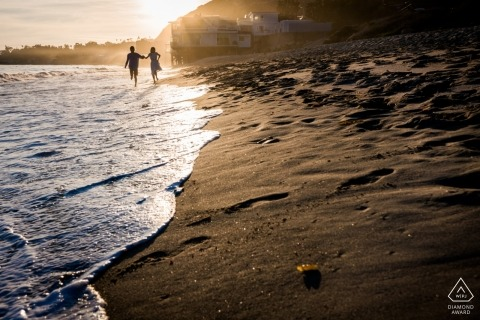 Engaged couple walking along Malibu beach during their pre-wedding session