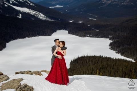 Der Verlobungsfotograf von Banff National Park, AB, Kanada, hat dieses Foto eines Paares aufgenommen, das sich auf einem schneebedeckten Berg befindet