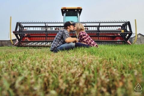 Ein Paar sitzt im Gras und küsst sich vor einem Traktor auf diesem Foto vor der Hochzeit eines Fotografen aus Alberta, Kanada.