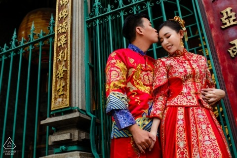 Ho Chi Minh City - This engagement portrait of a couple holding hands outside of a gate was captured by an engagement photographer