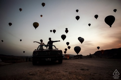 Sihouetted air balloons fly around the enagged couple during their pre-wedding session in Turkey, Cappadocia