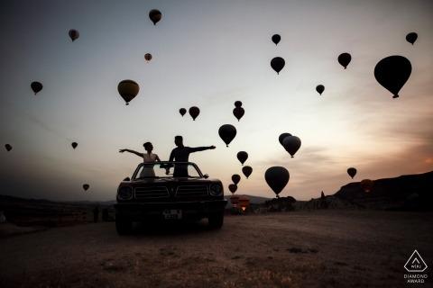 Sihouetted luchtballonnen vliegen rond het enagged paar tijdens hun pre-huwelijkszitting in Turkije, Cappadocia